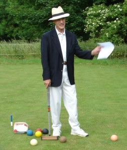 A gent playing croquet on the lawn